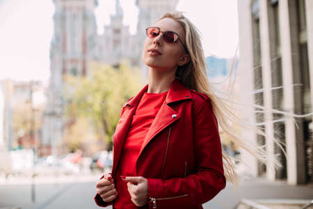 portrait of beautiful young blonde in the city. Hair develops in the wind. Dressed in red leather jacket.