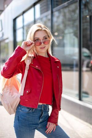 Outdoor portrait of cute blonde lady wears elegant red jacket.girl looks out from under fashionable colored glasses 版權商用圖片