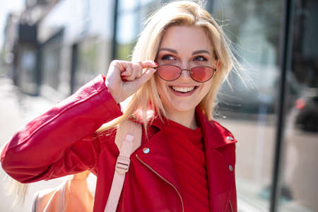 Closeup selfie-portrait student of attractive girl in sunglasses with long hairstyle and snow-white smile.Outdoor portrait of cute blonde lady wears elegant red jacket Imagens - 148097471