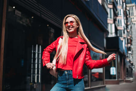 Well-dressed lady in good mood playfully posing on city background.Outdoor portrait of cute blonde lady wears elegant red jacket