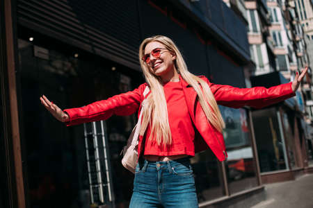 Emotional blonde woman posing with happy smile on the street. young sexy hipster girl enjoying photoshoot on city background