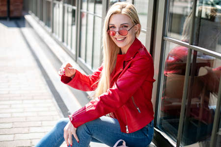 girl looks out from under fashionable colored glasses. Smiling blonde woman laughing on the street cheerfully. Lovely young lady feeling happy 版權商用圖片