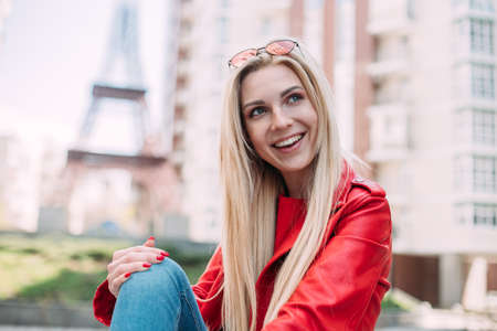 Closeup selfie-portrait student of attractive girl in sunglasses with long hairstyle and snow-white smile. Outdoor portrait of cute blonde lady wears elegant red jacket