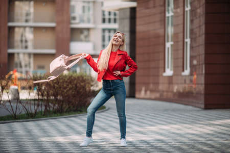 Emotional blonde woman posing with happy smile on the street.Girl student throws backpack.