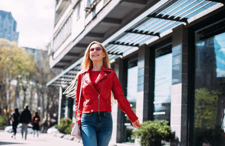 Young beautiful woman in leather jacket and jeans looking in camera walking around city street Smiling blonde woman laughing on the street cheerfully. Lovely young lady feeling happy