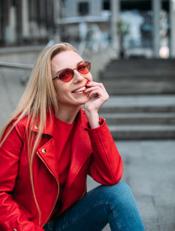 Nice girl in trendy red leather jacket looking at camera.