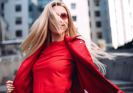 Beautiful woman wearing sunglasses Hair fluttering in the wind. Smiling blonde woman laughing on the street cheerfully. Lovely young lady feeling happy