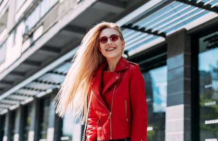 Young pretty stylish woman posing at city. trendy casual outfit, magnificent positive lady .Outdoor portrait of cute blonde lady wears stylish red jacket.