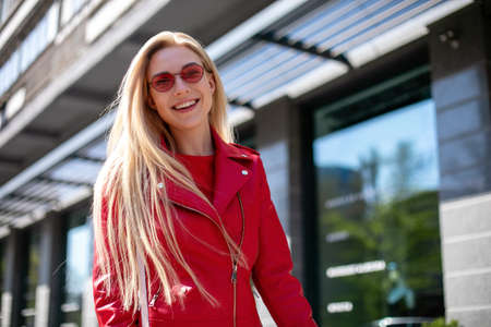 young stylish girl enjoys summer and vacation.Outdoor portrait of cute blonde lady wears elegant red jacket.