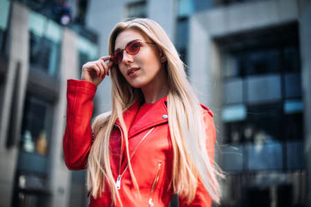 close-up portrait of a young sexy hipster girl.Outdoor portrait of cute blonde lady wears stylish red jacket.
