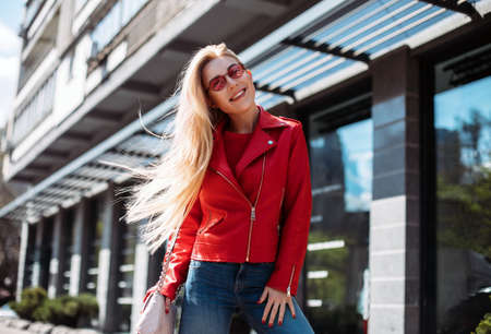 happy young stylish girl in leather jacket and jeans looking in camera walking around city street.beautiful blonde with long hair charmingly smiling.