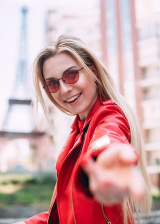 Ecstatic white female model making selfie in good day. Outdoor portrait of cute blonde lady wears elegant red jacket.girl is calling for herself