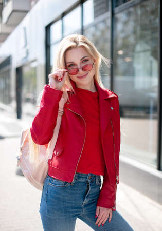 Fashion style portrait of young beautiful smiling young woman wearing a red leather jacket, posing at city street with magnificent architecture. Full body portrait.