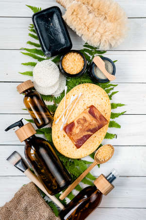 Eco friendly products. skin care cosmetics. lotion, body oil, mask, bath salt, face sponges, handmade soap, face sponge, bamboo brush on fern leaves. Spa composition.