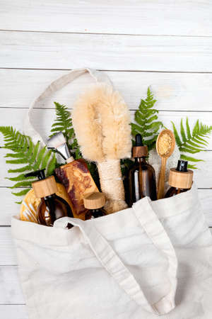 cotton bag with Eco-friendly cosmetics and zero waste set for spa on white background top view.skin care products. lotion, body oil, mask, bath salt handmade soap in white bag