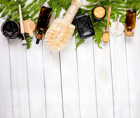 organic spa concept with various eco friendly cosmetic. Skin care products with lotion, body oil, mask, bath salt handmade black soap, bamboo brush. Copy space for your text Imagens