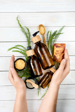 Beauty background with various eco friendly cosmetic zero waste concept. woman hands hold skin care products.lotion, body oil, mask, bath salt.
