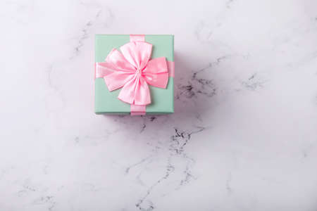 Pink box with ribbon and bow on a marble background. top view.space for text