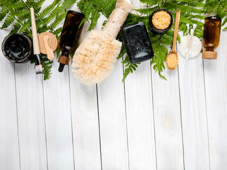 Spa composition. Eco friendly products. skin care cosmetics. lotion, body oil, mask, bath salt, handmade soap, bamboo brush on fern leaves. Concept spa background