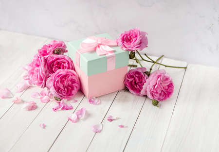 rose flowers and gift box with bow ribbon on white table. Greeting card for Birthday, Womans or Mothers Day