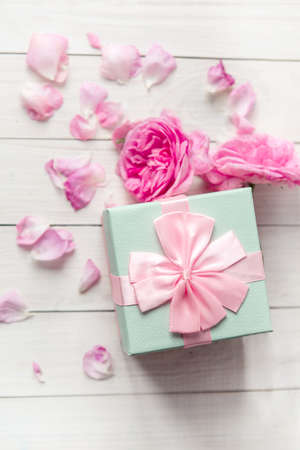 rose flowers and gift box with bow ribbon on light table. Greeting card for Birthday, Womans or Mothers Day. top view
