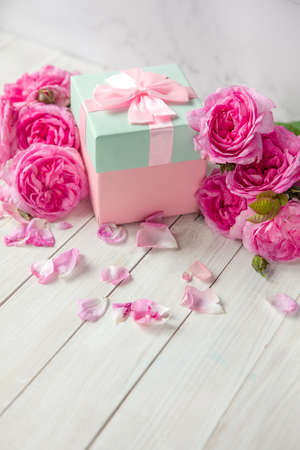 pink gift box surrounded by roses.gift box with bow ribbon on white table. Greeting card for Birthday, Womans or Mothers Day Imagens