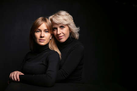 Mom and daughter . Beautiful woman 50 years old blonde and girl hugging. They are in sweaters on a black background in the studio. Emotional family photo. Imagens