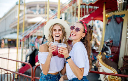 Two young beautiful girls have fun in an amusement park. Drink lemonade and laugh. ladies enjoying weekend together.