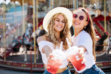 Appealing long-haired girls posing on amusement park background. Laughing ladies enjoying weekend together.