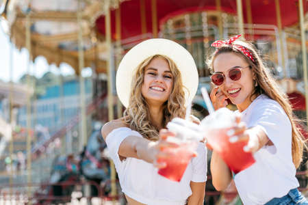 Two young beautiful girls have fun in an amusement park. Drink lemonade and laugh. ladies enjoying weekend together