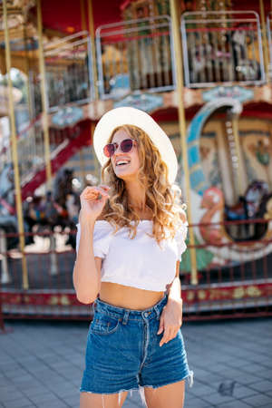 Beautiful blonde woman wearing sunglasses close-up portrait of a young sexy girl hipster in the park attraction.