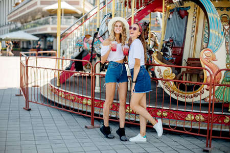 Closeup fashion lifestyle portrait of two pretty best friends girls, wearing bright swag style hats, mirrored sunglasses, having fun and make crazy funny faces. Two sisters posing on party
