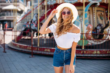 Beautiful blonde woman wearing sunglasses close-up portrait of a young sexy girl hipster in the park attraction.Stylish happy young woman wearing short denim shorts and a white T-shirt Imagens