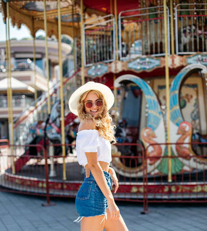Pretty happy young woman having fun.stylishly dressed in short denim shorts and bright t-shirts, sunglasses.