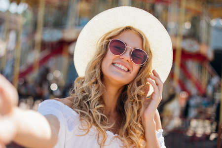 Joyful smiling girl in pink sunglasses making selfie in front of carousel. Outdoor portrait of cute stylish woman having fun in amusement park and taking selfie.