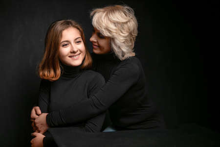 Joyful mother and daughter , hugging and enjoying. Studio photography on a black background. Emotional family photo Imagens