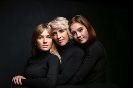 Family close-up portrait. Mom and two daughters are hugging and looking at the camera. They are in sweaters on black background in the studio. Emotional family photo Imagens