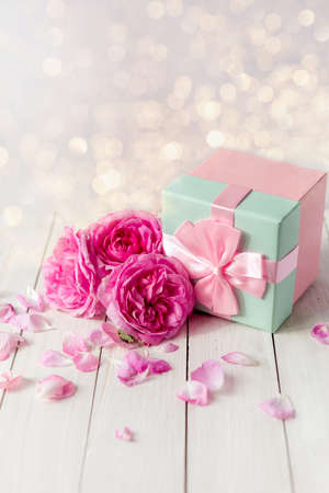 pink gift box surrounded by roses. gift box with bow ribbon on white table. Greeting card for Birthday, Womans or Mothers Day.