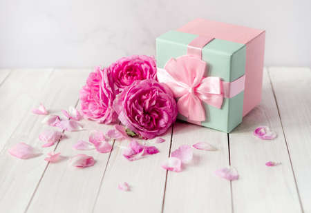 rose flowers and gift box with bow ribbon on light table. Greeting card for Birthday, Womans or Mothers Day.