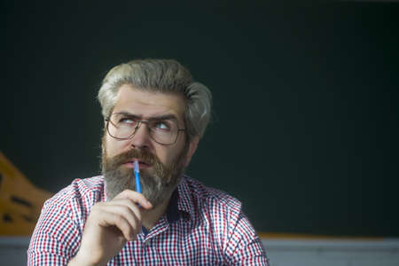 Portrait of thoughtful senior caucasian man with a grey beard and holding pen.