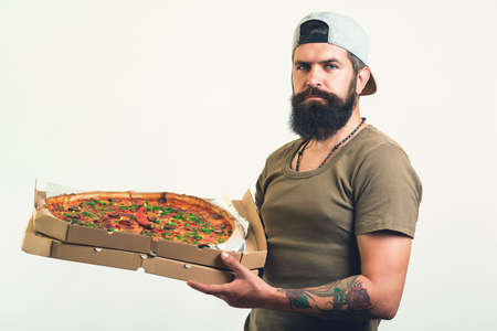 Handsome courier holds cardboard boxes with pizza, suggests taste delicious fast food, wears hat and t shirt. Stock fotó