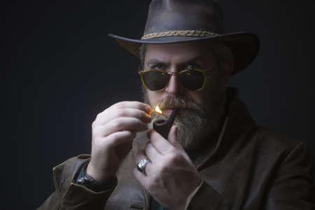 Menacing vintage cowboy standing with pipe for smoking. Studio shot against dark background. Stock Photo