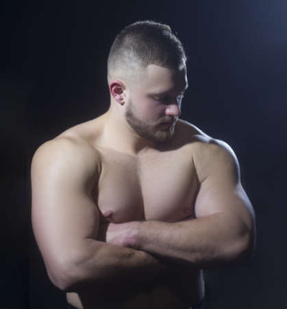 Strong athletic man fitness model torso showing big muscles over black background. Stock Photo