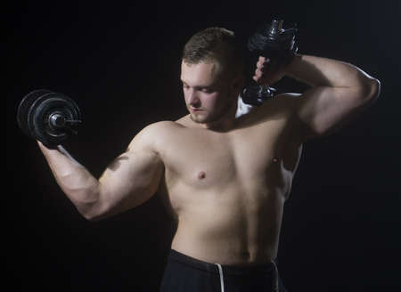 Fitness - big powerful muscular man lifting weights.