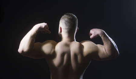 Muscled big male model showing his back.