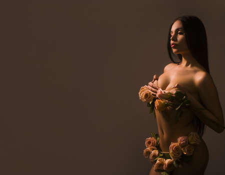 Beauty portrait. Beautiful brunette woman in sensual in underwear made with roses. Banque d'images