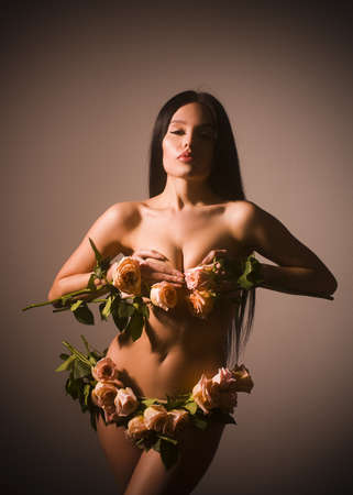 Beautiful young woman with long curly hair posing with roses instead of underwear.