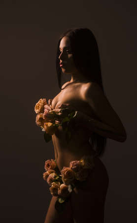 Model girl body with roses. Perfect skin. Perfume. Magazine cover.