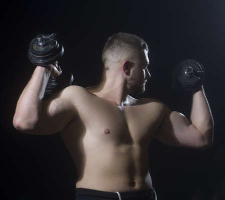 Muscular model young big man on dark background. Stock Photo