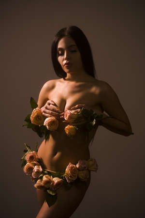 Beauty portrait of seductive brunette woman with perfect body with pink roses.